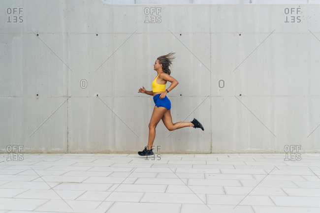 Female jogger in front of grey wall