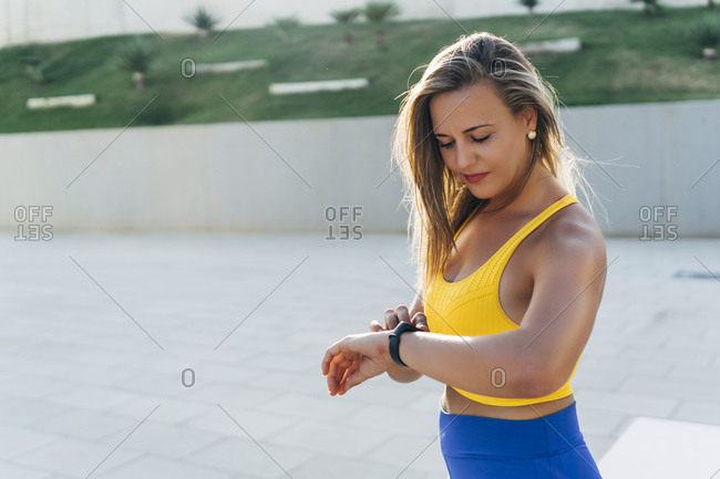 Young blond woman checking smartwatch