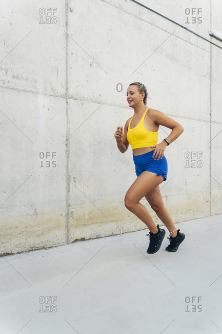 Female jogger in front of wall