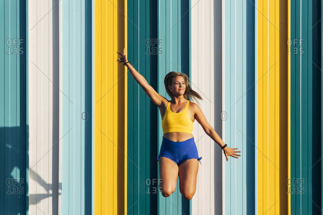 Blond athletic woman jumping in front of colorful wall