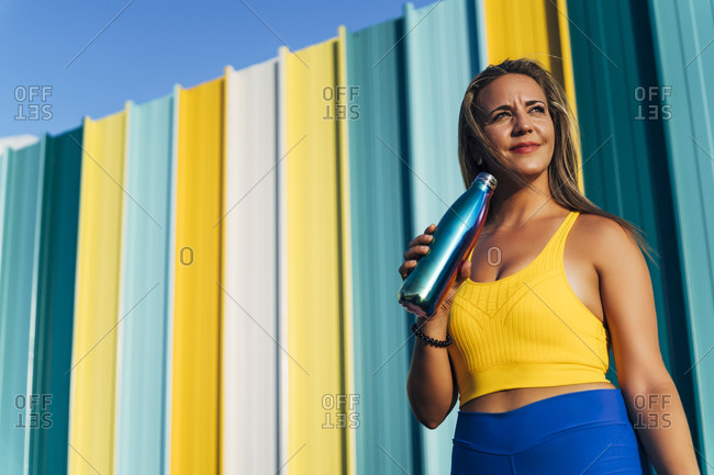 Female jogger with vacuum flask in front of colorful wall