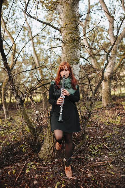 Beautiful young woman practicing clarinet while leaning on bare tree trunk in forest