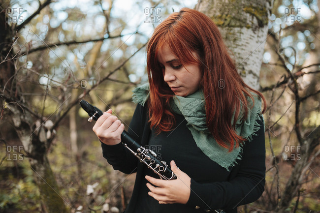 Beautiful young redhead female musician looking at clarinet while standing in forest
