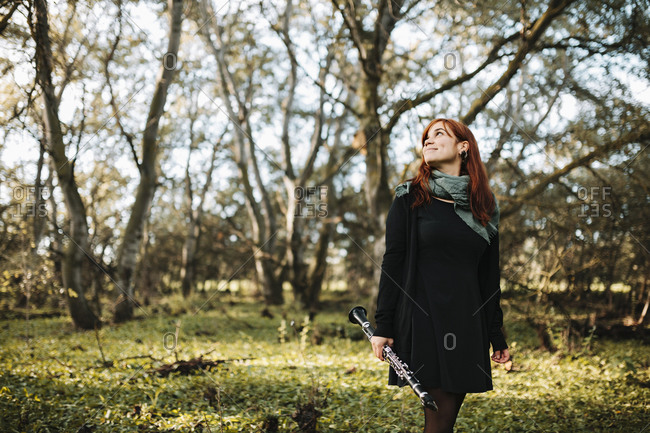 Young smiling woman holding clarinet while looking up and walking in forest