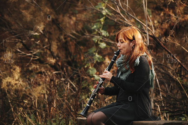 Beautiful redhead female musician practicing playing clarinet while sitting on bench in forest