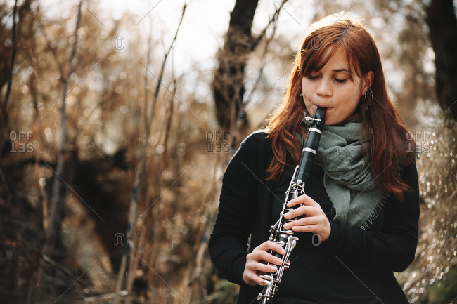 Beautiful redhead woman practicing clarinet in forest
