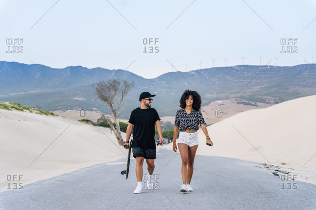 Smiling multi-ethnic couple walking on road amidst sand dunes against clear sky