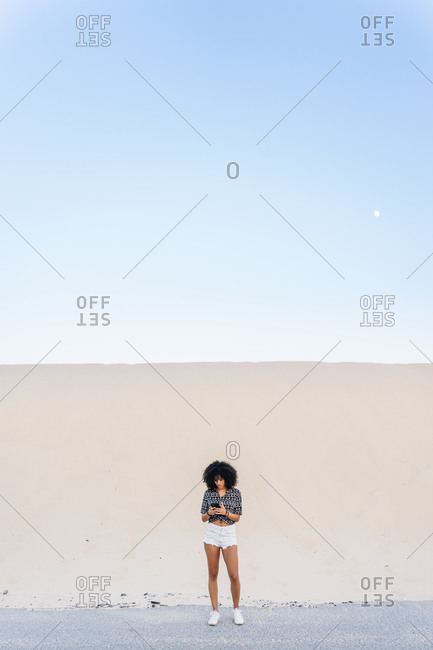Young woman using mobile phone while standing on road against sand dune