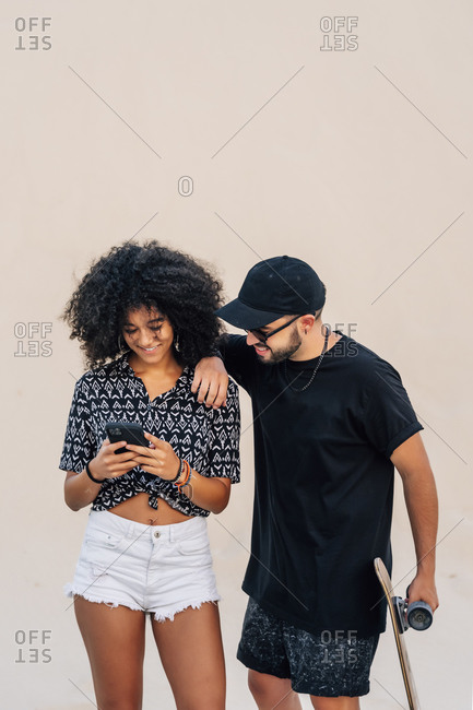 Smiling man standing and looking at woman using smart phone against sand dune