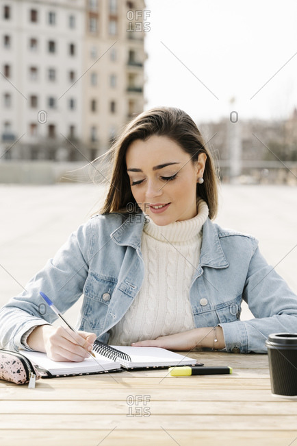 Young woman studying at table in university campus