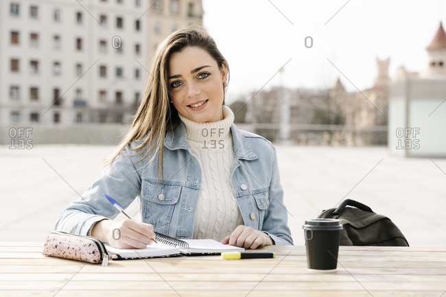 Smiling woman studying at table in university campus