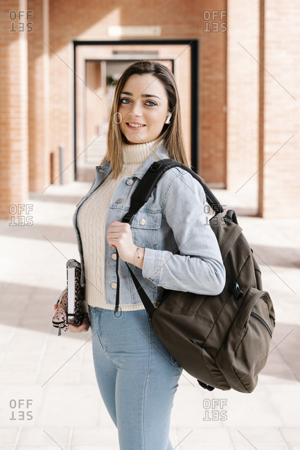 Smiling student with bag and book standing in university campus