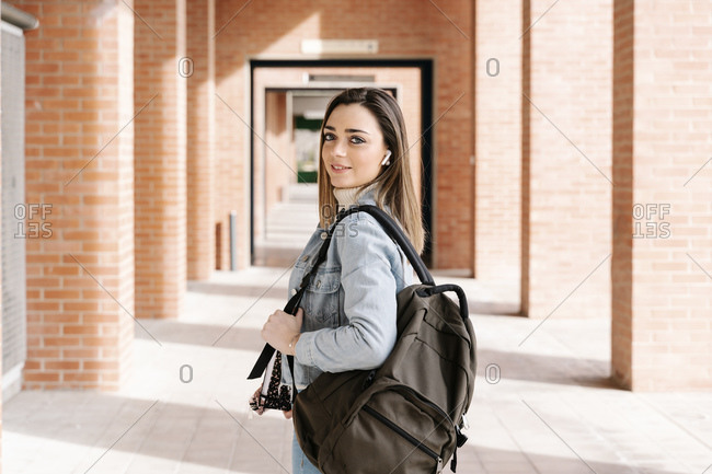 Smiling university student with bag and book standing in campus