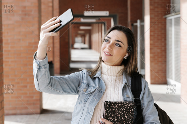 Smiling university student with book taking selfie in campus