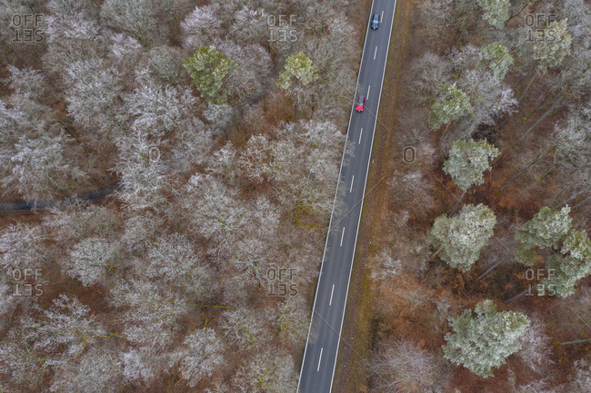 Germany- Bavaria- Drone view of cars driving along asphalt road cutting through Steigerwald forest in winter