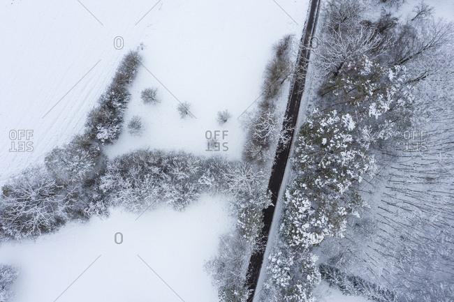 Drone view of asphalt road cutting through snow-covered forest inFranconianHeights