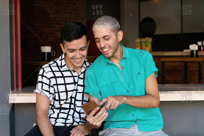 Gay man pointing while sharing mobile phone with friend while sitting restaurant counter
