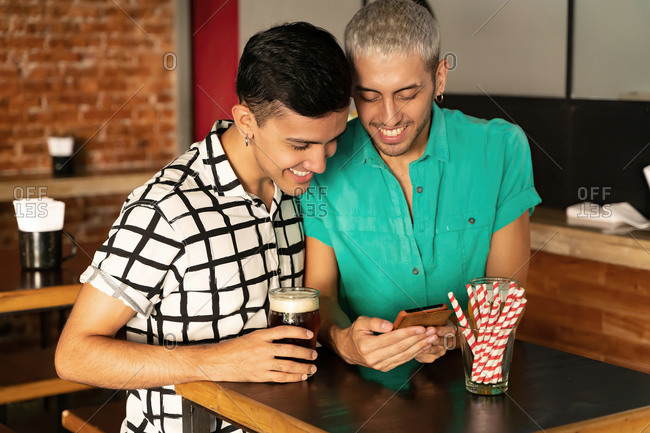 Gay couple sharing mobile phone standing at table in bar