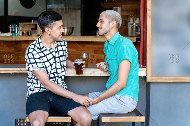 Loving gay couple holding hands while sitting at bar counter