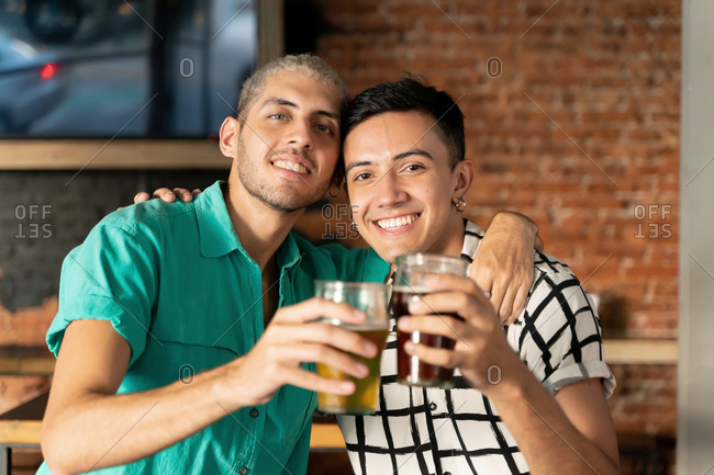Happy gay couple with arm around holding beer glass at bar