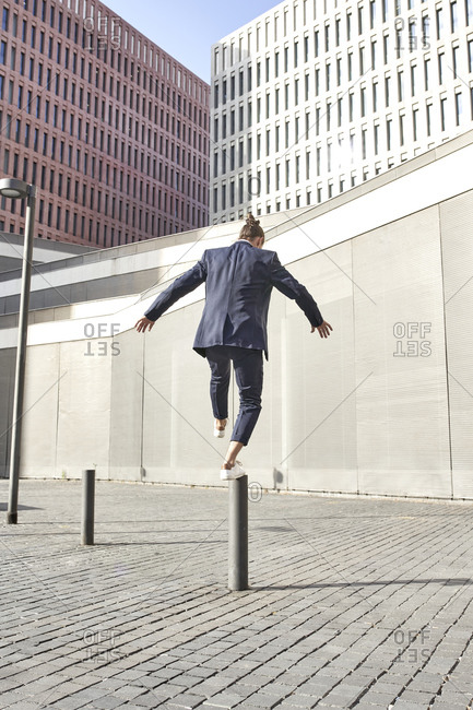 Businessman balancing on pole in city