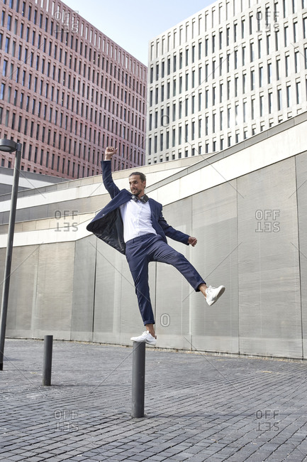 Happy businessman balancing on pole in city