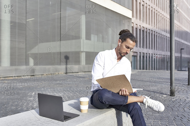 Businessman reading file while sitting on block in city