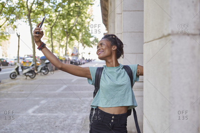 Happy young woman taking selfie by column on sidewalk