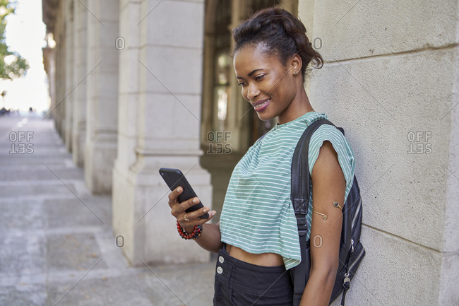 Smiling woman using phone while standing against column in city
