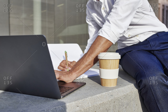 Businessman with laptop and disposable cup writing while sitting in city