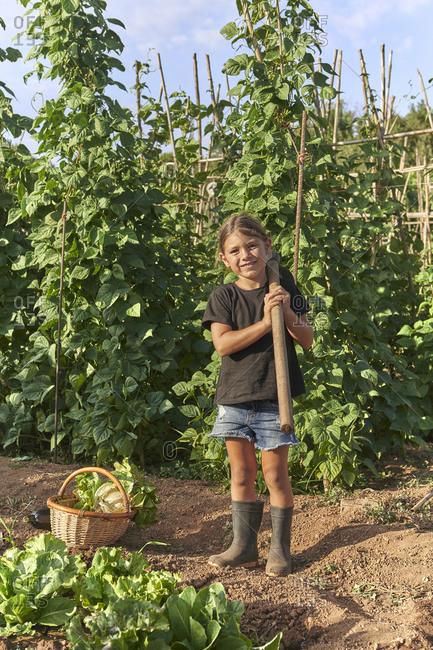 Girl standing with hoe in garden