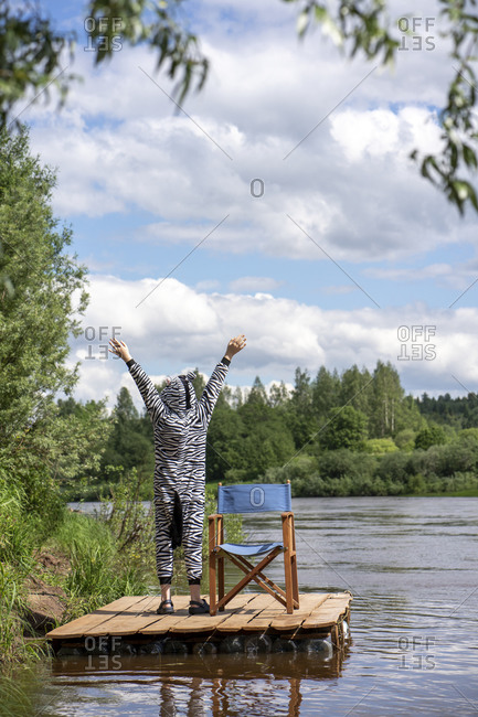 Boy in zebra costume with hands raised standing by lake