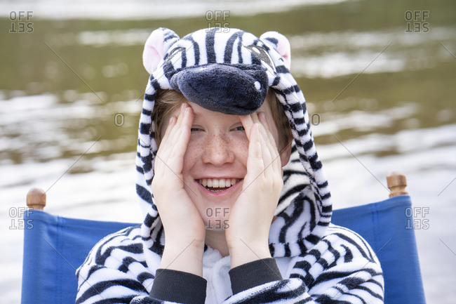 Smiling boy in zebra costume sitting on chair against lake