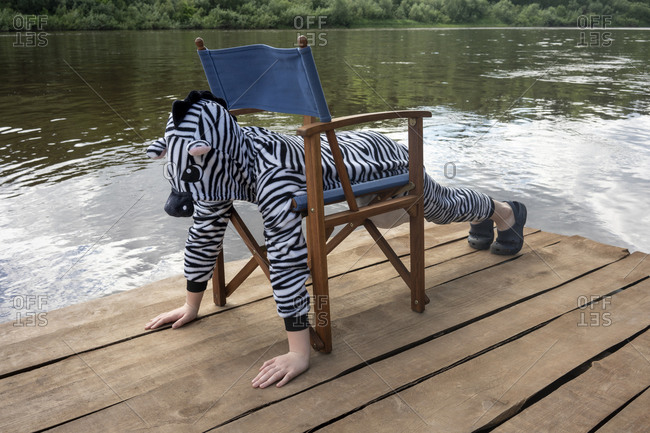 Boy in zebra costume exercising on chair over boardwalk