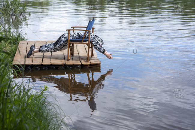 Boy wearing zebra costume exercising on chair by lake