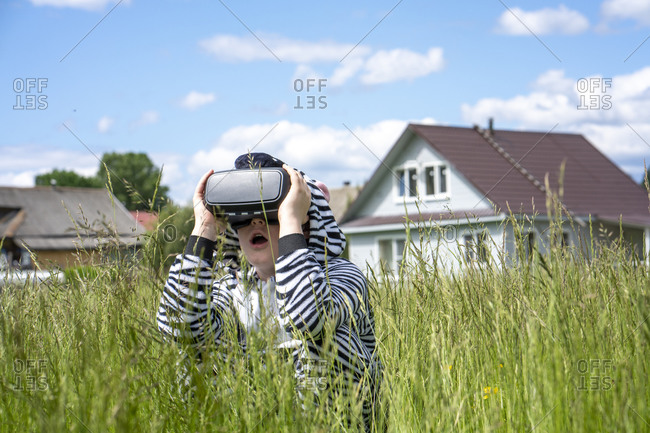 Boy wearing zebra costume using VR simulator amidst grass in city