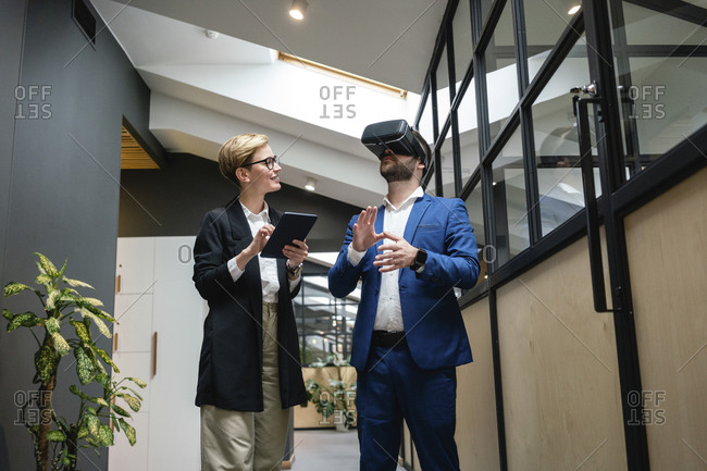 Businesswoman analyzing colleague using virtual simulation headset in creative office corridor
