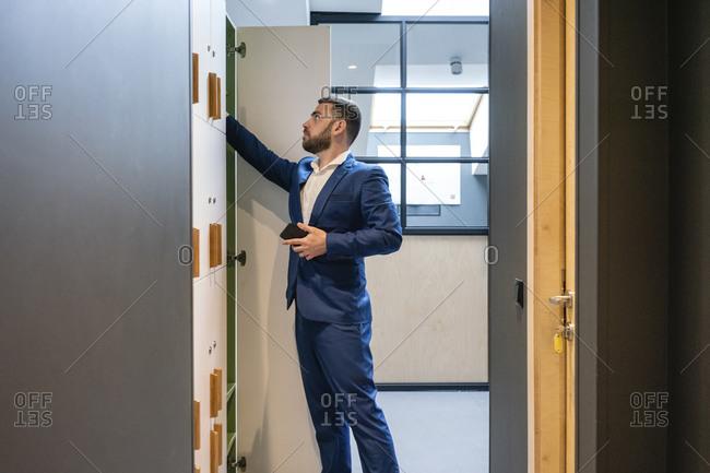 Bearded businessman searching something in locker room