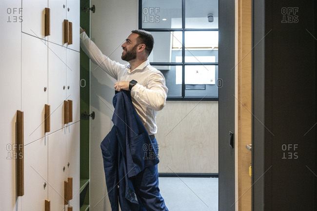 Smiling male professional holding suit while searching in locker