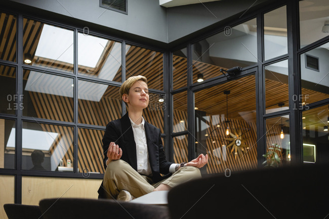 Businesswoman meditating while practicing yoga on table at coworking office space