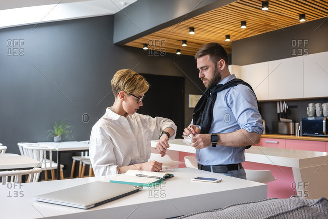 Worried businesswoman checking time while standing by businessman at creative coworking office