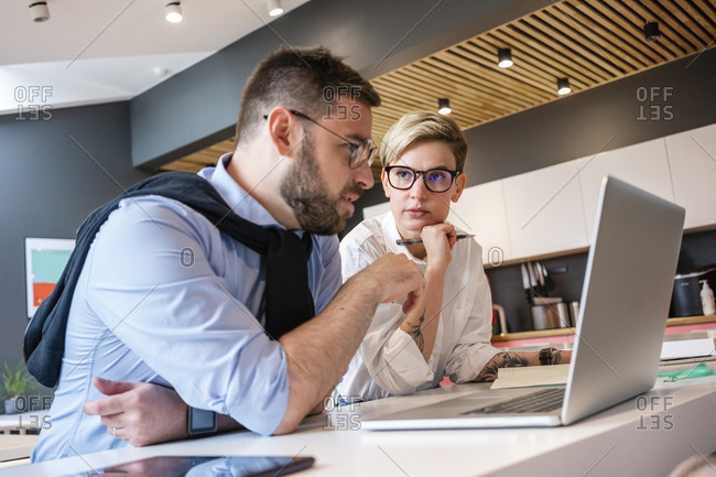 Confident male and female professionals planning strategy while discussing over laptop in office