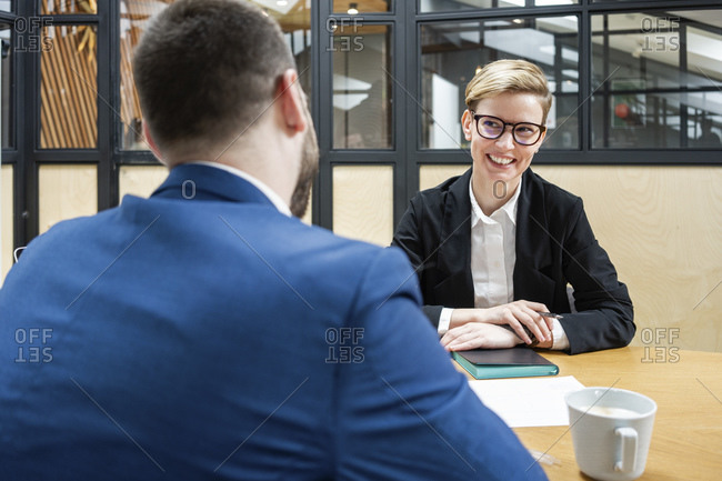Smiling businesswoman looking at male executive sitting in board room during job interview