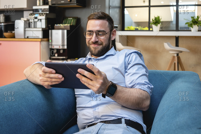 Smiling businessman using digital tablet for video call while sitting on armchair at office cafeteria
