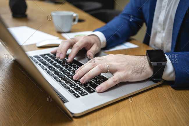 Close-up of businessman typing while using laptop at desk in creative coworking space