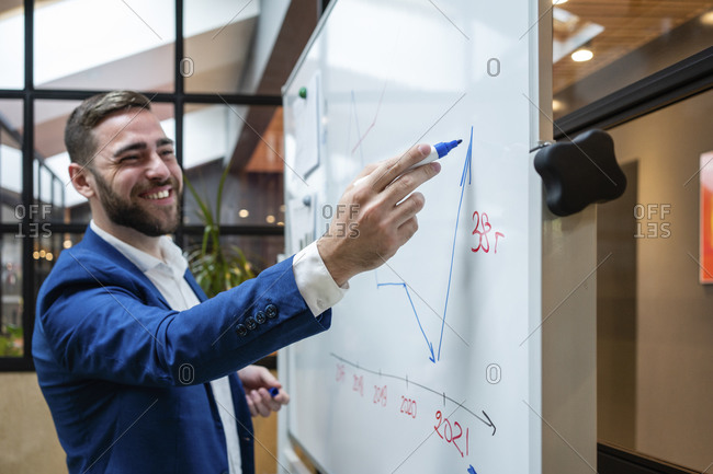 Smiling handsome businessman drawing graph on whiteboard during meeting in board room at office