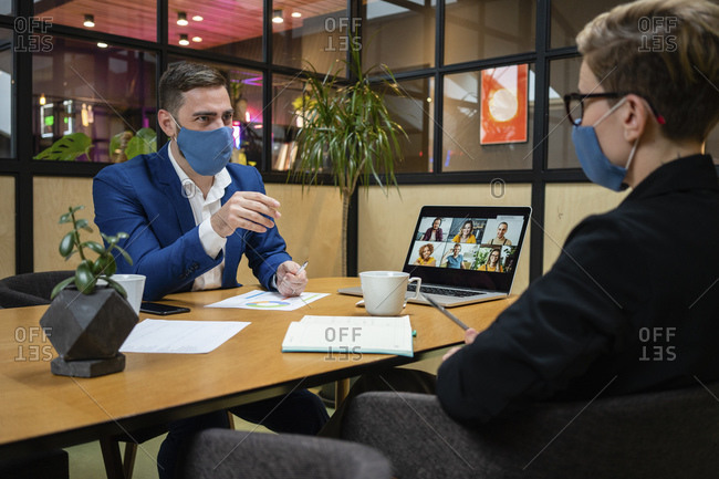 Male and female entrepreneurs wearing masks while planning strategy in board room during pandemic