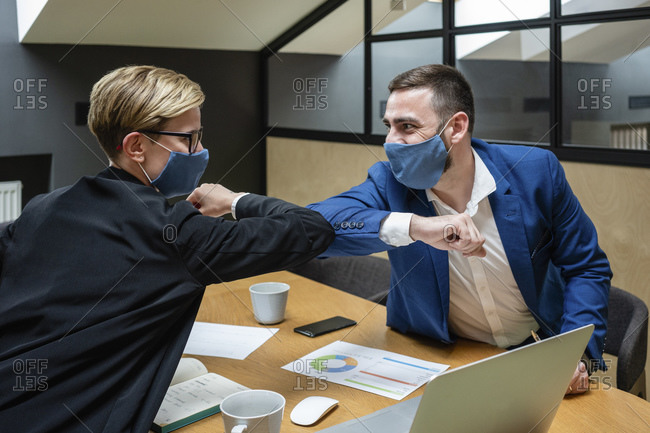 Male and female entrepreneurs wearing masks while greeting with elbow bump in board room during coronavirus pandemic