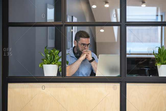 Thoughtful handsome male entrepreneur looking at laptop seen through glass wall in illuminated office