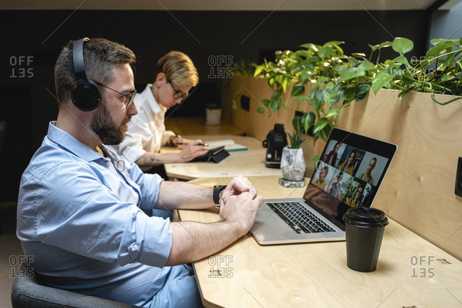 Businessman on video call with colleagues through laptop while sitting by businesswoman at desk in creative office